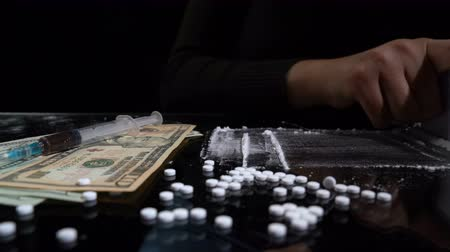 kokaina : White cocaine powder on a table with dollar bills and a syringe Wideo