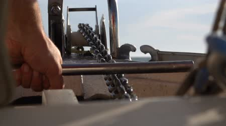 ancla : On a yacht they raise the anchor chain with an anchor using a winch. Slow motion