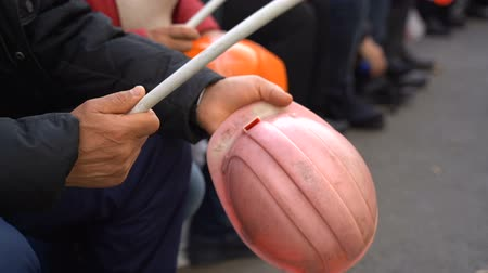 labour : Workers baton with protective orange helmet for protests. Slow motion. Video with sound
