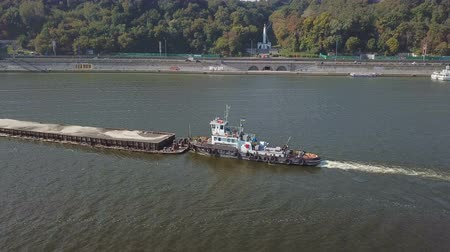 waterways : Towing boat pulls a large barge with sand on the Dnieper River in Kiev Ukraine. Aerial survey