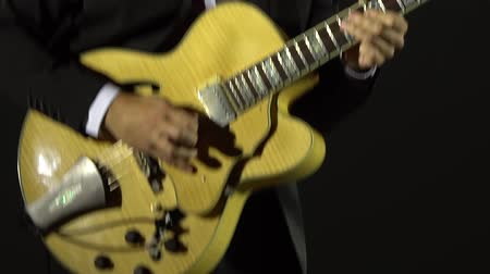 smokin : The musician plays a semi-acoustic electric guitar on a black background. Close-up. Slow motion Stok Video
