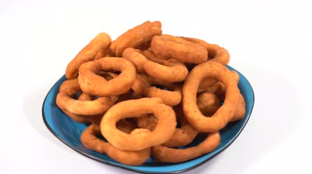 rosquinhas : A lot of fresh fried doughnuts in a plate on the table spinning in front of the camera