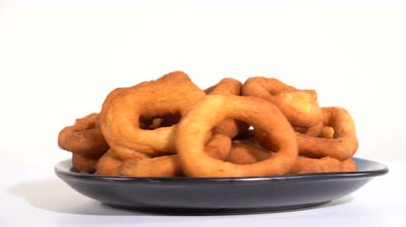 застекленный : A lot of fresh fried doughnuts in a plate on the table spinning in front of the camera