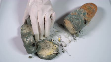 hijenik olmayan : Mouldy white bread is cut with a knife on a white table. Close-up