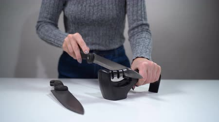 apontador : A girl sharpens a knife with a sharpener on a white table