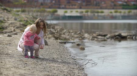 fur boots : Mother and child on a river bank outdoors