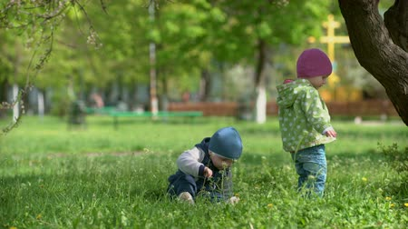 small park : Two small children on the grass under a tree