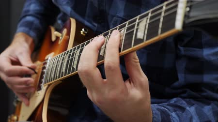 hmatník : Man playing on guitar. Fingers on guitar fretboard playing chords and solo. Musical instruments concept. Professional guitar lessons. Musician playing jazz and blues