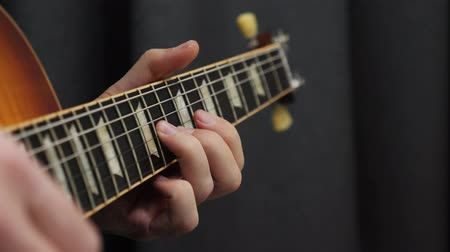 rocker : Human fingers playing on guitar. Close up of guitar fretboard and male hand playing chords. Professional guitar solo. Music lessons with teacher