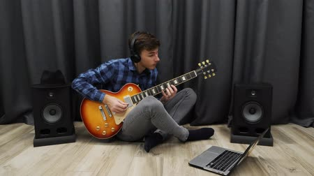 amplificador : Man learning to play on guitar. Young male in headphones playing on electric guitar using notebook. Teenager sitting on floor at living room and learning chords on guitar