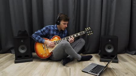amplificador : Man in headphones playing on guitar and singing. Professional musician practicing the song on electric guitar and singing sitting in living room. Guitar music lessons