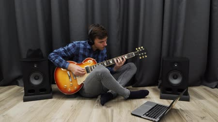 amplificador : Human learning to play on guitar. Man in headphones practicing to play on electric guitar. Young teenager playing on guitar while sitting on floor at living room