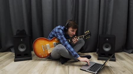 amplificador : Man in headphones playing on guitar. Young guitarist performing the song on electric guitar and enjoying playing. Happy smiling musician practicing on guitar while sitting on floor at home