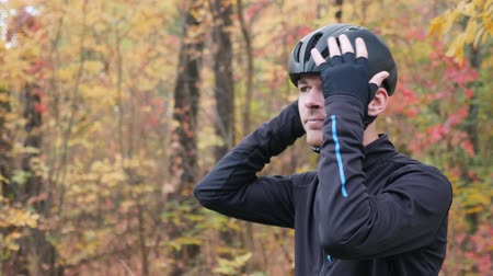 bisikletçi : Motivated young male cyclist preparing for training in fall city park. Side view portrait of professional sportsman in cycling apparel puts on black helmet and sports glasses. Slow motion