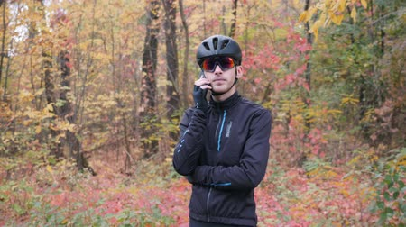 veiligheidsbril : Young professional male cyclist talking on phone before workout on bike in fall park. Attractive nervous cycling guy speaking on phone in autumn forest before training. Slow motion