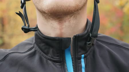застежка : Professional male cyclist closing zipper on jacket and helmet clasp before outdoors workout on bike in autumn forest. Extra close up front view of young athlete preparing for training. Slow motion Стоковые видеозаписи