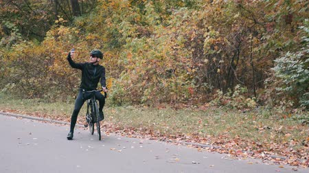 racers : Young handsome professional triathlete in black cycling clothes, black helmet and glasses on road bicycle in autumn forest taking selfie on phone. Triathlon concept. Male cyclist