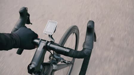 спринт : Road bicycle handlebar. Bike details. Bicycle wheel. Male hand holding bike handlebar and riding in city park. Slow motion