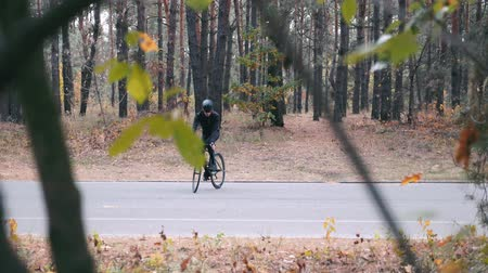 спринт : Concentrated young professional athlete in cycling apparel, helmet and sports sunglasses standing in track on road bike in autumn park. Handsome triathlete having fun on bicycle in fall forest Стоковые видеозаписи