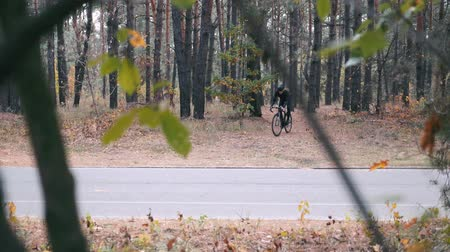 veiligheidsbril : Fit good-looking professional cyclist in black cycling apparel, helmet and sunglasses riding on cyclocross bike in autumn park. Young handsome male athlete preparing for cycling race. Slow motion
