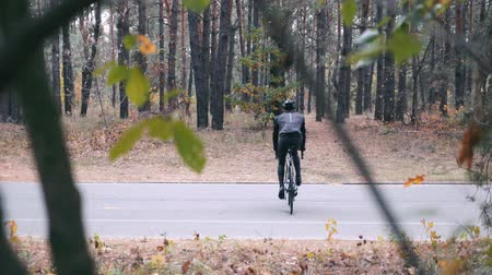 ciclismo : Young stylish professional male cyclist in black helmet and sports sunglasses pedaling on cyclocross bike through autumn park. Rear view of triathlete intensive training on bicycle at fall. Slow motion