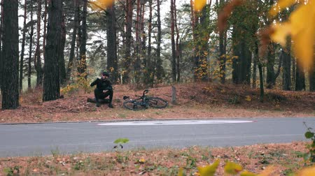 cinematic : Confident handsome professional male triathlete in helmet and sunglasses sitting in fall park, resting after hard training on road bike and drinking water. Autumn cycling workouts outdoor