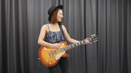 rockero : Woman playing on electric guitar against gray background. Female musician practicing to play on guitar. Pretty girl in hat playing on music instrument in studio Archivo de Video