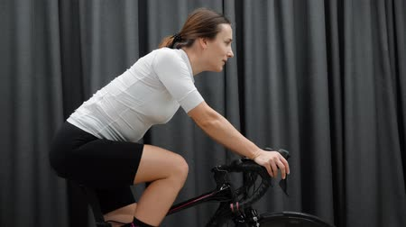 педаль : Young Fit woman cycling indoors on stationary bicycle side view. Cycling workout on indoor smart trainer side view. Стоковые видеозаписи