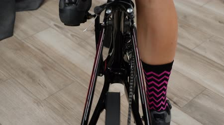педаль : Legs pedaling on indoor smart trainer. Woman legs hard pedaling while training indoors on stationary bike with pedals and chainring.