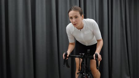 stationary : Beautiful motivated female cycling out of saddle on smart home indoor cycle trainer wearing white outfit. Indoor cardio training concept Stock Footage