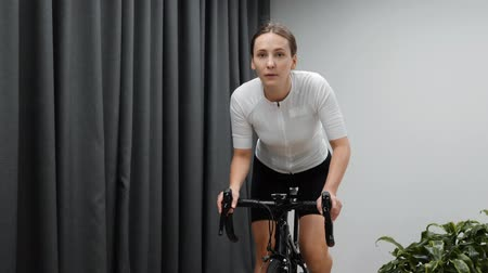 estacionário : Woman cycling indoors on stationary bicycle. Focused female doing fitness hardio workout on indoor smart cycling trainer,