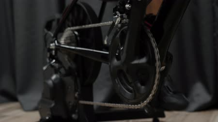 cassette : Legs, chain and chainring with rear cassette pedaling on smart indoor bicycle trainer. Professional indoor cycling concept.