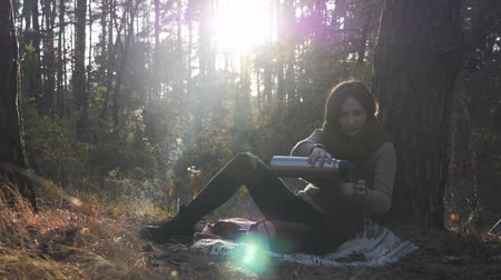kufel : Young brunette caucasian woman in warm sweater and scarf sitting on plaid in fall forest and pouring and drinking tea from thermos Wideo