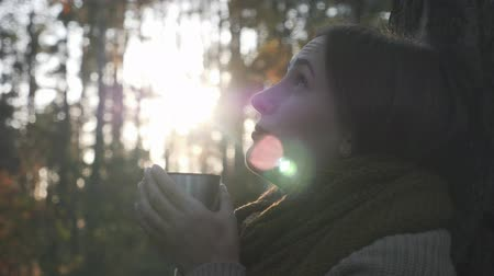 センチメンタル : Extra close up view of young sentimental female traveler holding cup of hot drink and looking to the sky in autumn forest at sunset