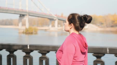 スリミング : Close up view of young chubby female doing nordic walking along city river with bridge on background. Weight loss concept