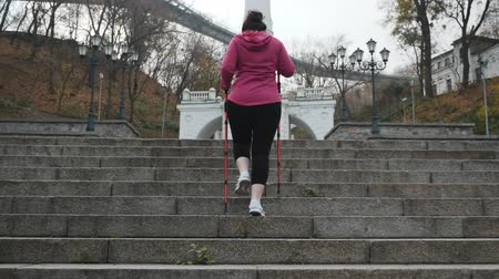スリミング : Nordic Walking. Young adult doing nordic walking exercises in city going up the stairs. Cardio outdoor activity
