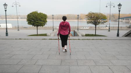 wandelstok : Nordic walking. Back follow shot of chubby female walking with sports poles in city with traffic and river on background