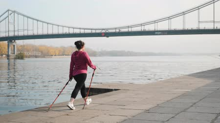 bengala : Fit chubby woman with nordic walking poles training in the morning for competition and marathon. Wellness concept