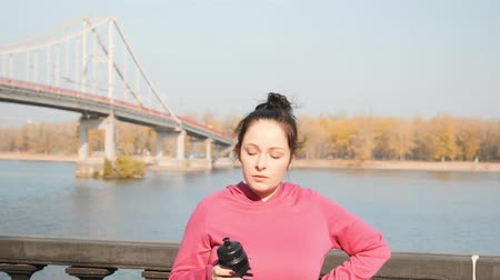 круглолицый : Close up view of beautiful motivated woman drinking water or isotonic drink after intensive outdoor running training Стоковые видеозаписи