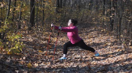 bengala : Stretching exercises with nordic walking poles before training in city autumn park. Weight loss concept