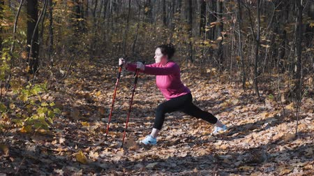 bengala : Young cute overweight woman with nordic walking poles stretching before intense training