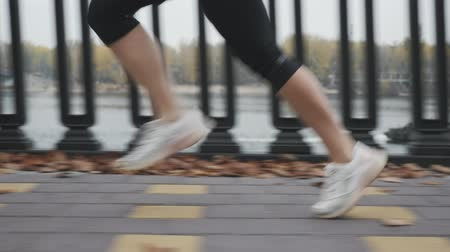 бегун трусцой : Professional female runner fast running and hard training before ultra marathon, close up side view of feet. Woman athlete is intense jogging on city promenade along river