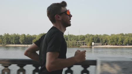 бегун трусцой : Young athletic man in black t-shirt and sports sunglasses jogging along river. Sportive active boy training on city embankment. Caucasian fit man doing outdoor exercises on city quay. Slow motion Стоковые видеозаписи