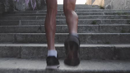 buzağı : Muscular strong tanned male legs run up stairs. Close up back view of sportive powerful male legs. Slim athletic man runs up stairs. Professional athlete in black outfit jogging up stairs. Slow motion