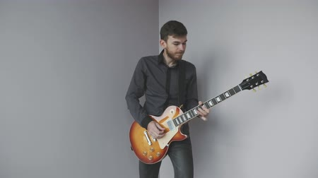 ゴージャス : Handsome caucasian rock guitarist with beard and gray shirt plays electric guitar isolated. Attractive male guitarist plays electric guitar. Music industry concept