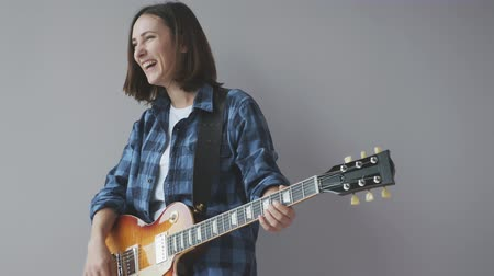 akord : Happy beautiful woman with electric guitar plays rock and blues song wearing blue casual shirt smiling and laughing. Rock guitar player practicing music