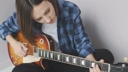 hmatník : Young attractive female with electric guitar practicing songs before concept. Hands playing on guitar fretboard pulling strings and chords. Music concept Dostupné videozáznamy