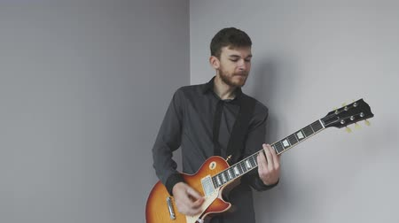 rocker : Young man with electric guitar playing and preparing for concert. Handsome man with beard holding guitar and playing rock and blues songs. Stock Footage