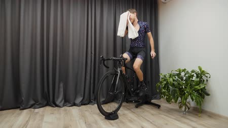 ciclismo : Cycling indoor workout on smart trainer. Male sweating while cycle training, unbuttoning jersey and holding towel. Cycling virtual concept