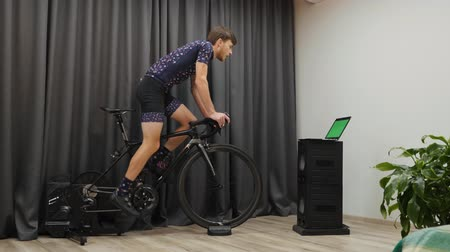 motivováni : Confident motivated male in bicycle apparel cycling out of saddle on home smart bike trainer. Man doing cycling exercises and preparing for race. Young athlete intensively pedaling on cycle indoor